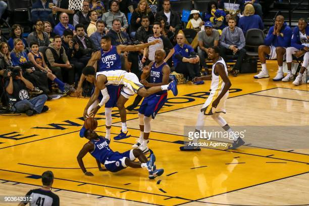 Jawun Evans and Wesley Johnson of LA Clippers in action against Patrick McCaw of Golden State Warriors during the NBA basketball game between LA...