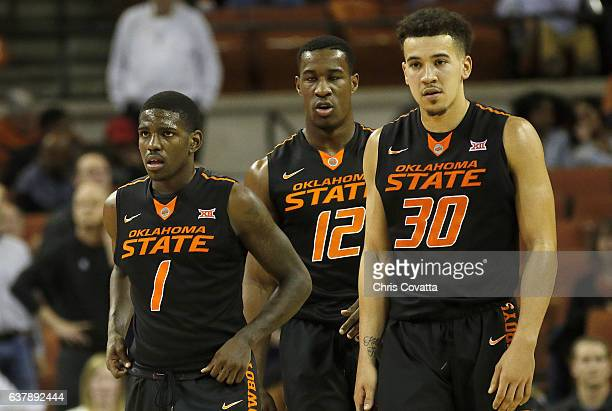 Jawun Evans Cameron McGriff and Jeffrey Carroll of the Oklahoma State Cowboys stand on the court during the game with the Texas Longhorns at the...