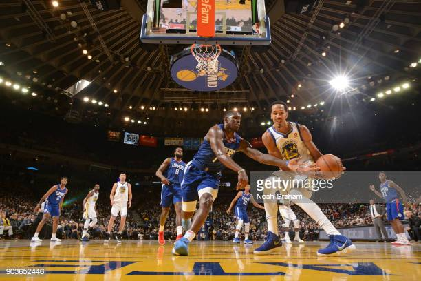 Jawun Evans of the LA Clippers and Shaun Livingston of the Golden State Warriors go for a loose ball on January 10 2018 at ORACLE Arena in Oakland...