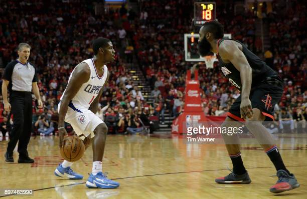 Jawun Evans of the LA Clippers controls the ball defended by James Harden of the Houston Rockets in the second half at Toyota Center on December 22...