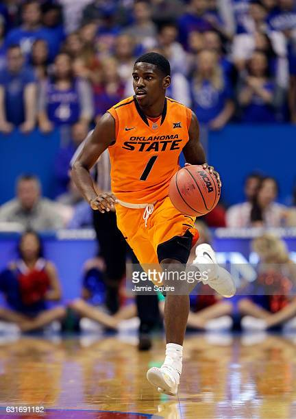 Jawun Evans of the Oklahoma State Cowboys controls the ball during the game against the Kansas Jayhawks at Allen Fieldhouse on January 14 2017 in...
