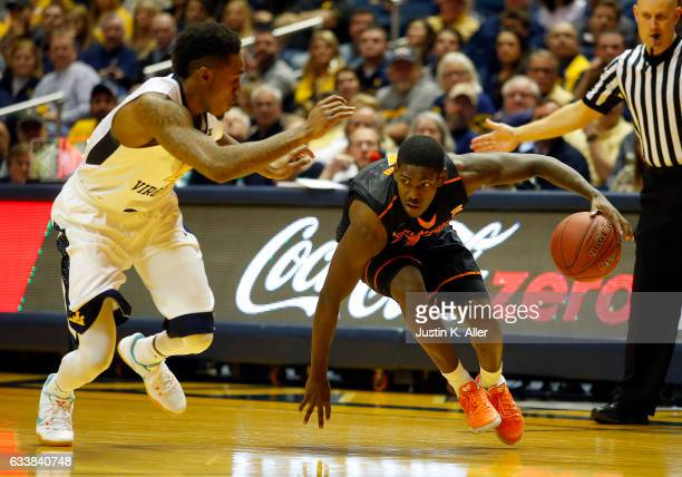 Jawun Evans of the Oklahoma State Cowboys drives the ball against Daxter Miles Jr #4 of the West Virginia Mountaineers at the WVU Coliseum on...