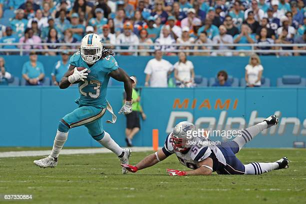 Jay Ajayi of the Miami Dolphins runs from the attempted tackle by Rob Ninkovich of the New England Patriots on January 1 2017 at Hard Rock Stadium in...