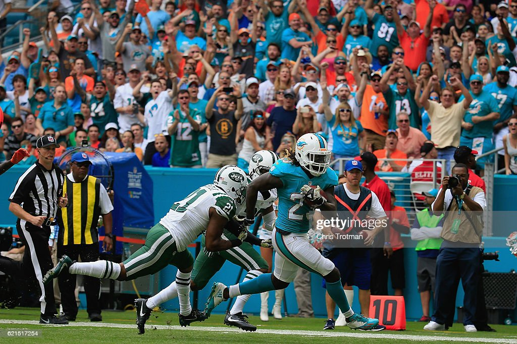 Jay Ajayi #23 of the Miami Dolphins rushes for a touchdown in the first quarter as Marcus Gilchrist #21 of the New York Jets looks on at the Hard Rock Stadium on November 6, 2016 in Miami Gardens, Florida.