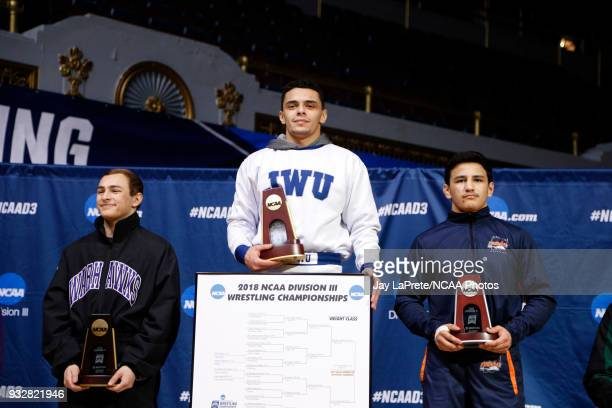 Jay Albis of Johnson Wales stands atop the podium after winning first place in the 125 weight class during the Division III Men's Wrestling...