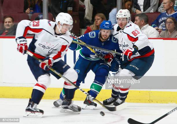 Jay Beagle and Christian Djoos of the Washington Capitals and Alex Biega of the Vancouver Canucks watch a loose puck during their NHL game at Rogers...