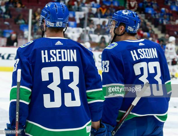 Jay Beagle and Justin Bailey of the Vancouver Canucks sport Henrik Sedin jerseys during warmup before their NHL game against the Chicago Blackhawks...