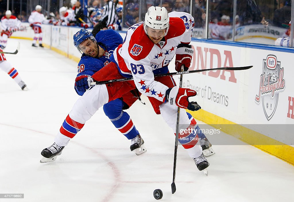 Jay Beagle #83 of the Washington Capitals battles for the puck against Dominic Moore #28 of the New York Rangers in Game One of the Eastern Conference Semifinals during the 2015 NHL Stanley Cup Playoffs at Madison Square Garden on April 30, 2015 in New York City.