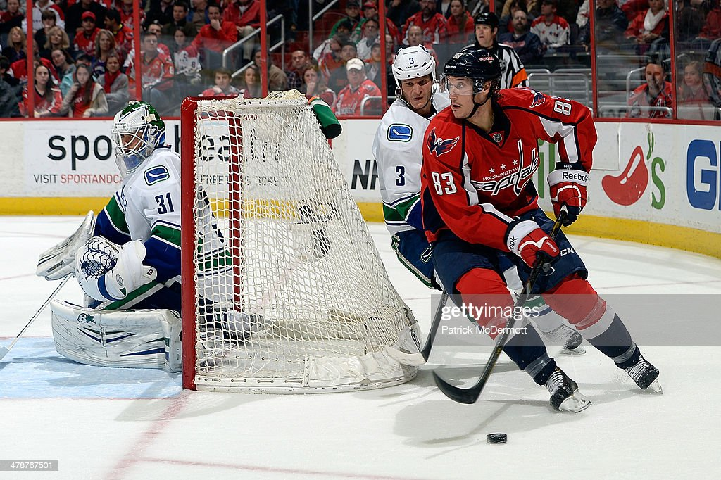 Jay Beagle #83 of the Washington Capitals brings the puck around the net against Kevin Bieksa #3 of the Vancouver Canucks in the third period during an NHL game at Verizon Center on March 14, 2014 in Washington, DC.