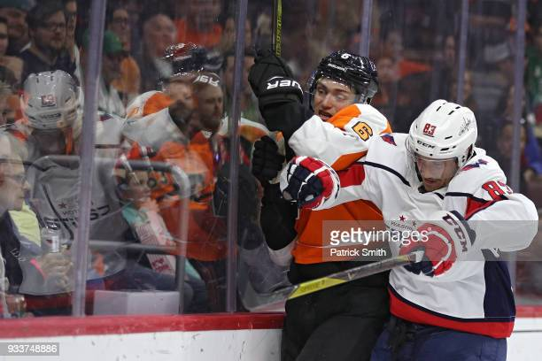 Jay Beagle of the Washington Capitals checks Travis Sanheim of the Philadelphia Flyers during the first period at Wells Fargo Center on March 18 2018...