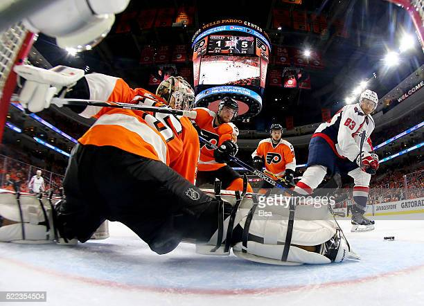 Jay Beagle of the Washington Capitals scores in the third period as Steve Mason and Shayne Gostisbehere of the Philadelphia Flyers defend in Game...