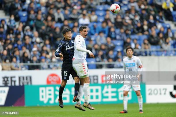 Jay Bothroyd of Consadole Sapporo and Yasuyuki Konno of Gamba Osaka compete for the ball during the JLeague J1 match between Gamba Osaka and...