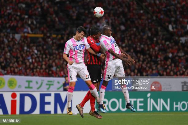 Jay Bothroyd of Consadole Sapporo competes for the ball against Kim Min Hyeok and Victor Ibarbo of Sagan Tosu during the JLeague J1 match between...