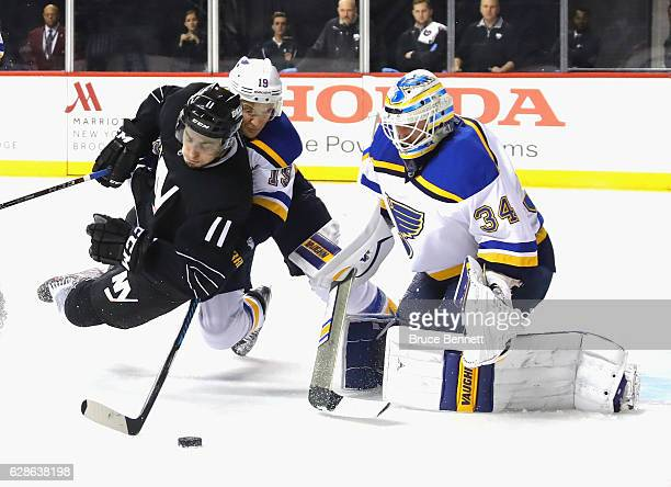 Jay Bouwmeester and Jake Allen of the St. Louis Blues defend against Shane Prince of the New York Islanders during the second period at the Barclays...