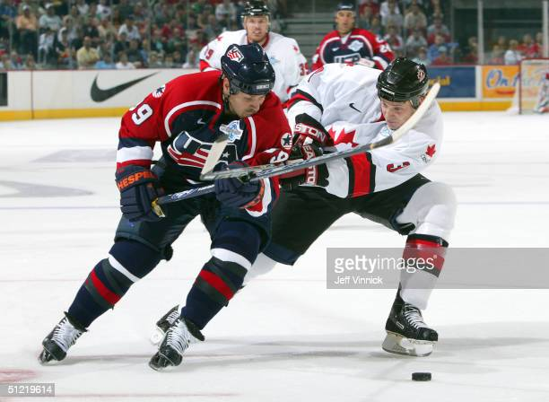 Jay Bouwmeester of Team Canada and Doug Weight of Team USA battle for the puck during the first period of their exhibition game in the World Cup of...