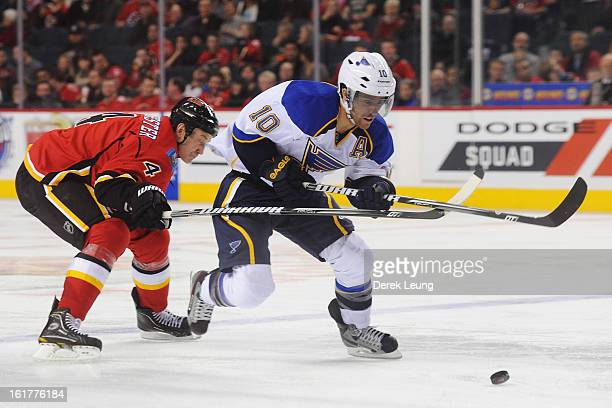 Jay Bouwmeester of the Calgary Flames tries to check Andy McDonald of the St Louis Blues during an NHL game at Scotiabank Saddledome on February 15...