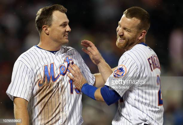 Jay Bruce and Todd Frazier of the New York Mets react between innings against the Philadelphia Phillies during a game at Citi Field on September 8...