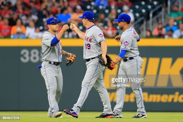 Jay Bruce celebrates with Michael Conforto and Juan Lagares of the New York Mets after beating the Atlanta Braves at SunTrust Park on June 10 2017 in...