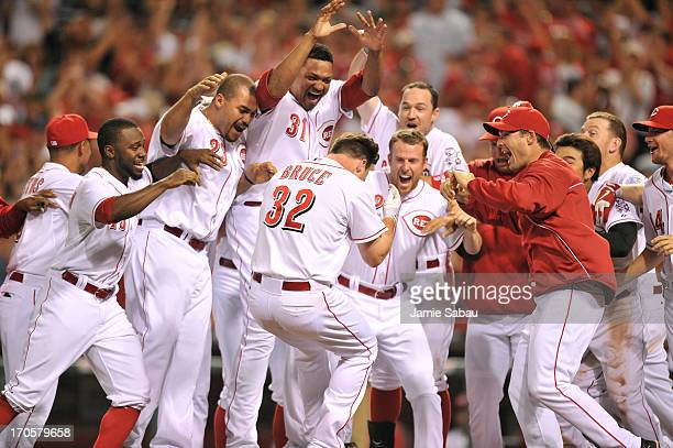 Jay Bruce of the Cincinnati Reds is mobbed as he crosses home plate after hitting a tenthinning walkoff home run to defeat the Milwaukee Brewers 43...