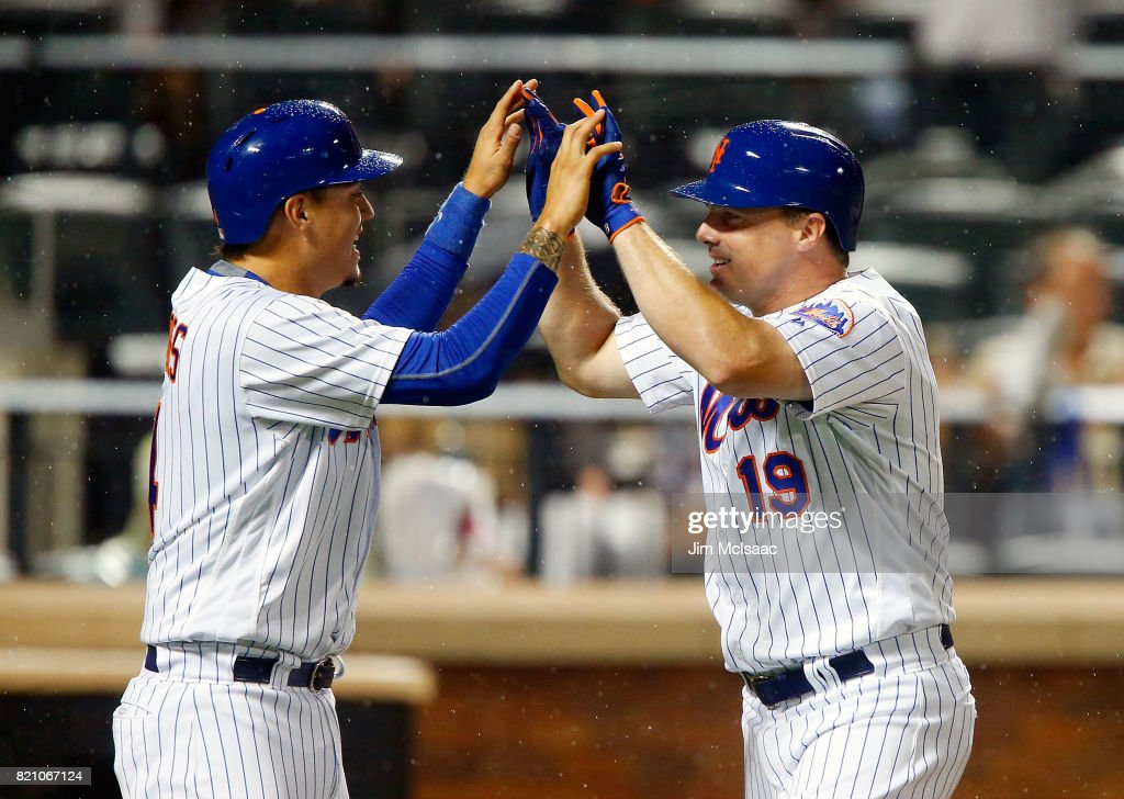 Jay Bruce #19 of the New York Mets follows celebrates his sixth inning two run home run against the Oakland Athletics with teammate Wilmer Flores #4 at Citi Field on July 22, 2017 in the Flushing neighborhood of the Queens borough of New York City.