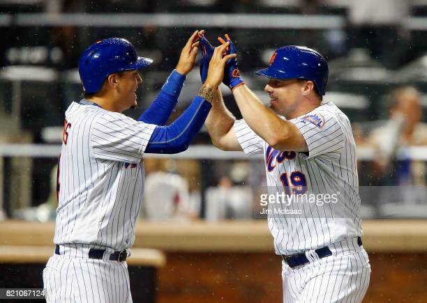 Jay Bruce of the New York Mets follows celebrates his sixth inning two run home run against the Oakland Athletics with teammate Wilmer Flores at Citi...