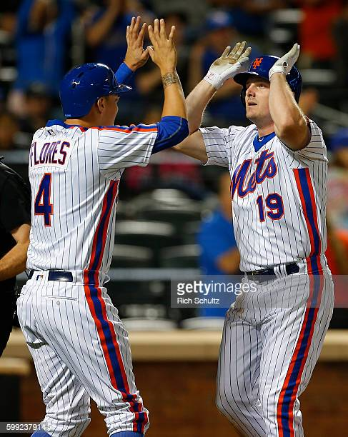Jay Bruce of the New York Mets is congratulated by Wilmer Flores after Bruce's two run home run against the Washington Nationals during the sixth...