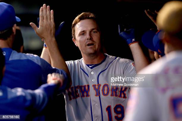 Jay Bruce of the New York Mets is congratulated in the dugout after hitting a home run in the fourth inning against the Colorado Rockies at Coors...