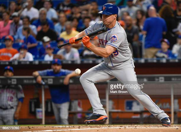 Jay Bruce of the New York Mets lays a bunt in the second inning against the Miami Marlins at Marlins Park on April 13 2017 in Miami Florida