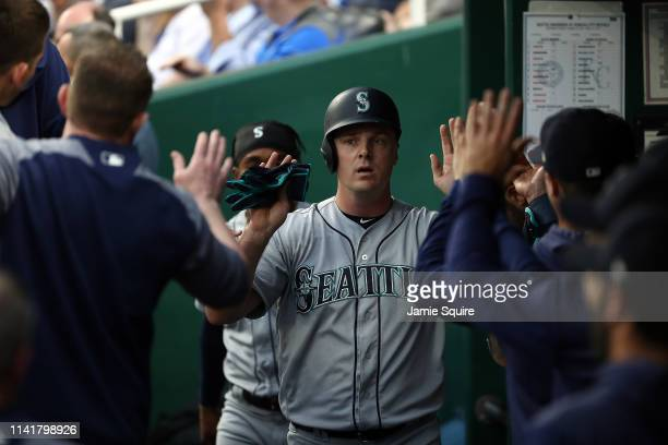 Jay Bruce of the Seattle Mariners is congratulated in the dugout after scoring during the 1st inning of the game against the Kansas City Royals at...
