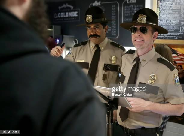 Jay Chandrasekhar left and Erik Stolhanske stars of the film 'Super Troopers 2' serve complimentary coffee and donuts to fans at Moody's Delicatessen...