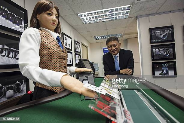 Jay Chun chairman of Paradise Entertainment Ltd stands for a photograph with Min a prototype humanlike electronic croupier at the company's...