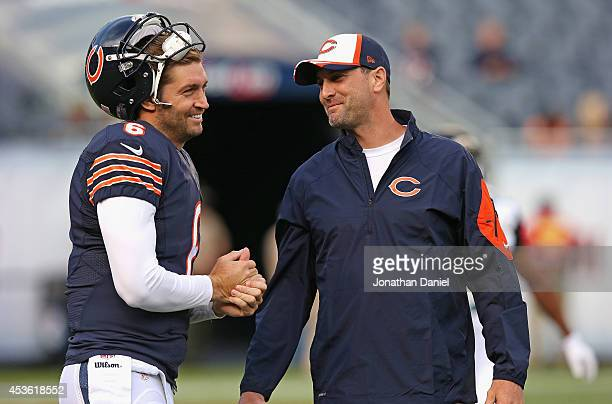Jay Cutler of the Chicago Bears talks with wide receivers coach Mike Groh during warmups prior to a preseason game against the Jacksonville Jaguars...