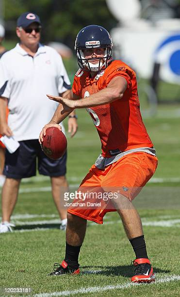 Jay Cutler of the Chicago Bears works out as offensive coordinator Mike Martz watches during a summer training camp practice at Olivet Nazarene...