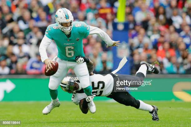 Jay Cutler of the Miami Dolphins is tackled by Rafael Bush of the New Orleans Saints in the first half during the NFL game between the Miami Dolphins...