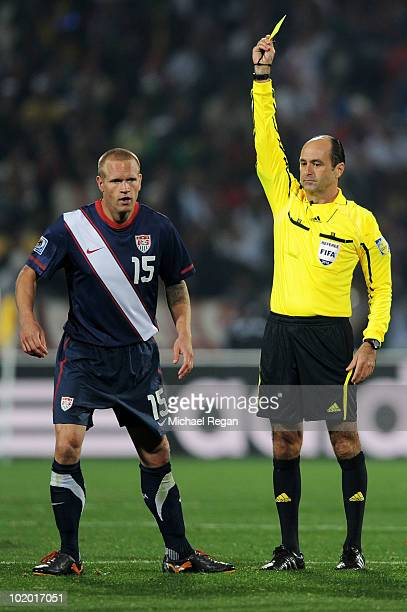 Jay Demerit of the United States is booked by Referee Carlos Simon during the 2010 FIFA World Cup South Africa Group C match between England and USA...