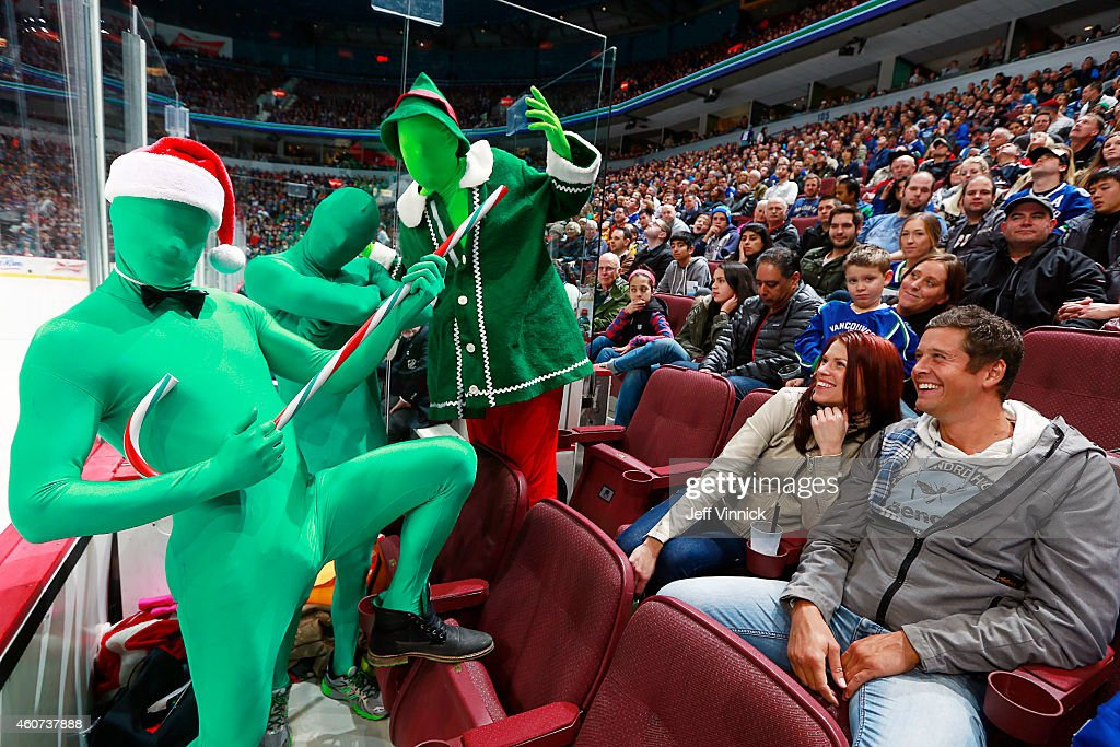 Jay DeMerit of the Vancouver Whitecaps FC (front) makes a guest appearance with The Green Men during the NHL game between the Vancouver Canucks and the Calgary Flames at Rogers Arena December 20, 2014 in Vancouver, British Columbia, Canada.