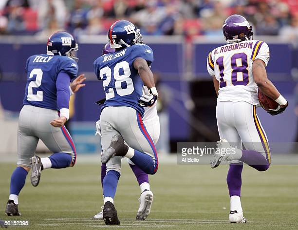 Jay Feeley and Gibril Wilson of the New York Giants chase Koren Robinson of the Minnesota Vikings who scored a touchdown on a kickoff return in the...