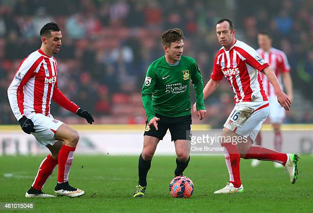 Jay Harris of Wrexham rus with the ball past Charlie Adam of Stoke City during the FA Cup Third Round match between Stoke City and Wrexham at...