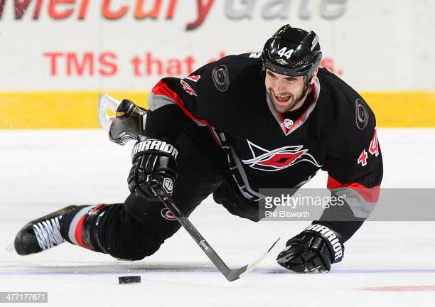 Jay Harrison of the Carolina Hurricanes attempts to control the puck as he falls to the ice during an NHL game against the New York Rangers on March...