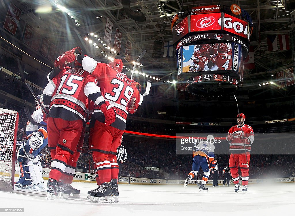 Jay Harrison #44 of the Carolina Hurricanes joins in the celebration with teammates Tuomo Ruutu #15 and Patrick Dwyer #39 following Dwyer's goal against the New York Islanders during their NHL game at PNC Arena on April 23, 2013 in Raleigh, North Carolina.