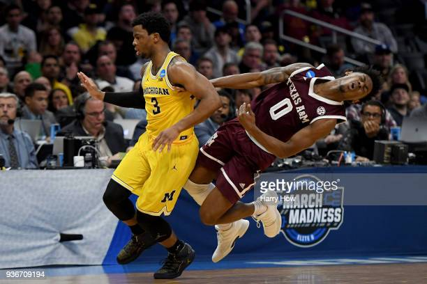 Jay Jay Chandler of the Texas AM Aggies reacts alongside Zavier Simpson of the Michigan Wolverines in the second half in the 2018 NCAA Men's...
