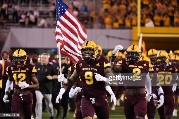 Jay Jay Wilson of Arizona State runs onto the field with teammates while carrying the US flag prior to a game against the University of Southern...