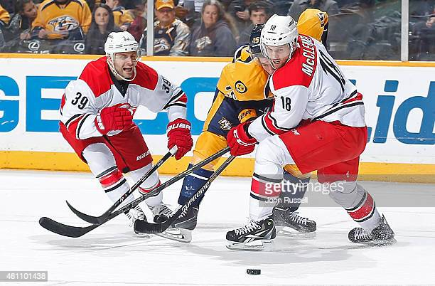 Jay McClement and Patrick Dwyer of the Carolina Hurricanes battle against Craig Smith of the Nashville Predators during an NHL game at Bridgestone...