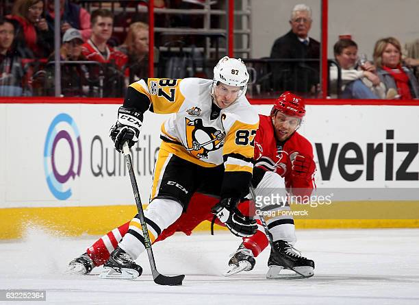 Jay McClement of the Carolina Hurricanes defends against Sidney Crosby of the Pittsburgh Penguins as he contorls the puck on the ice during an NHL...