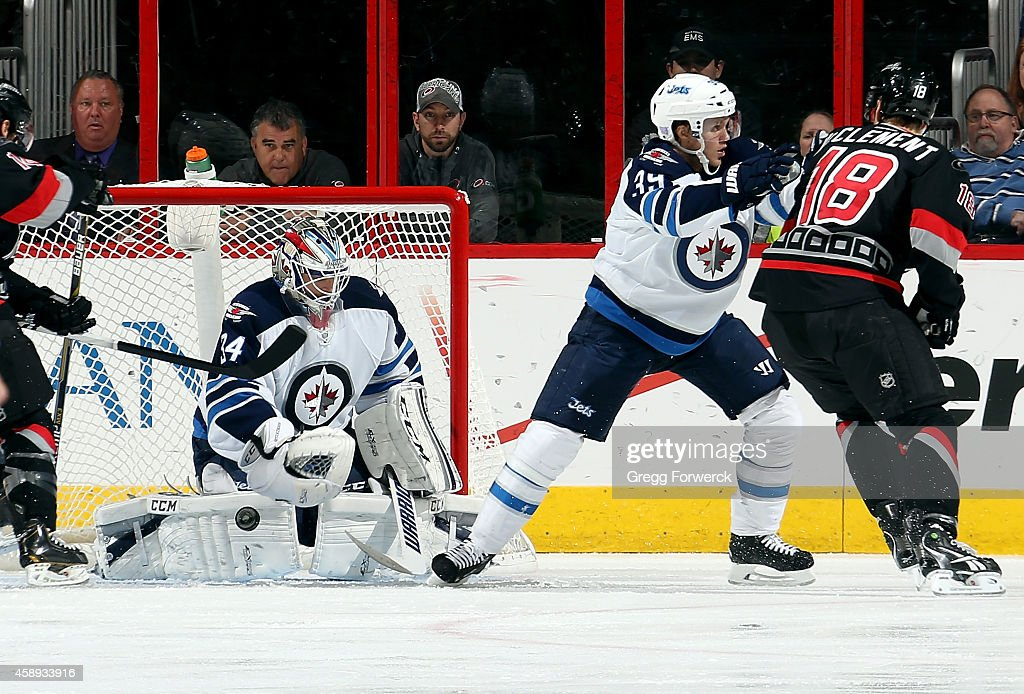 Jay McClement #18 of the Carolina Hurricanes is pushed away from the goal crease by Toby Enstrom #39 of the Winnipeg Jets as Michael Hutchinson #34 reacts to a loose puck during their NHL game at PNC Arena on November 13, 2014 in Raleigh, North Carolina.