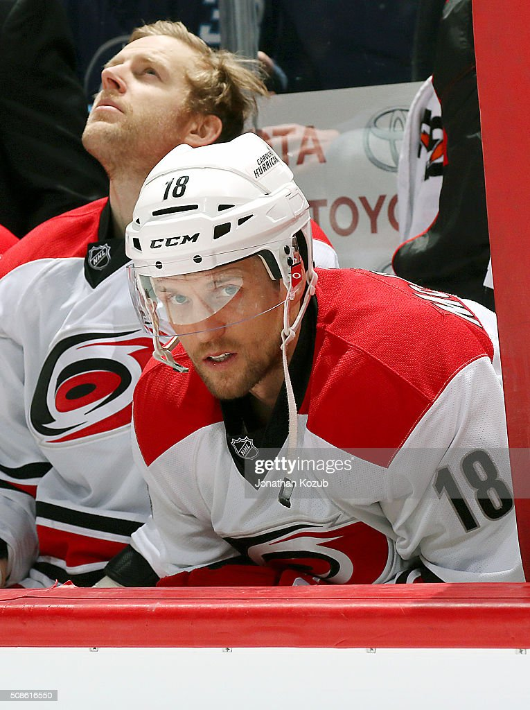 Jay McClement #18 of the Carolina Hurricanes looks on from the bench prior to puck drop against the Winnipeg Jets at the MTS Centre on February 5, 2016 in Winnipeg, Manitoba, Canada.