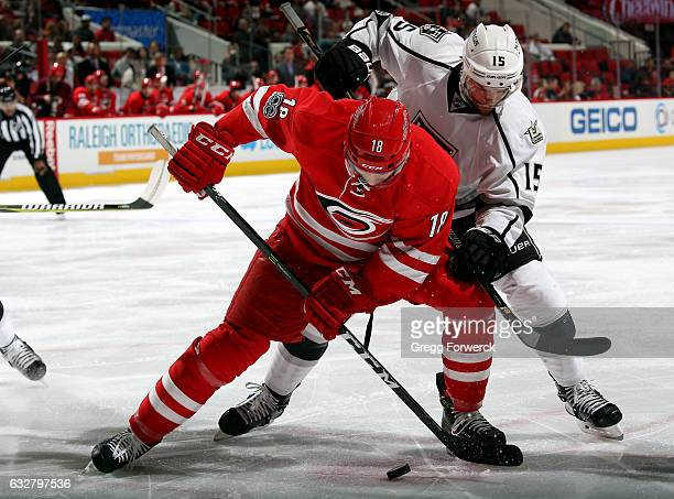 Jay McClement of the Carolina Hurricanes protects the puck from Andy Andreoff of the Los Angeles Kings after winning a faceoff during an NHL game on...