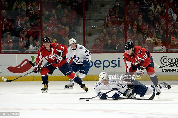 Jay McClement of the Toronto Maple Leafs battles for the puck against Mike Green of the Washington Capitals in the first period during an NHL game at...