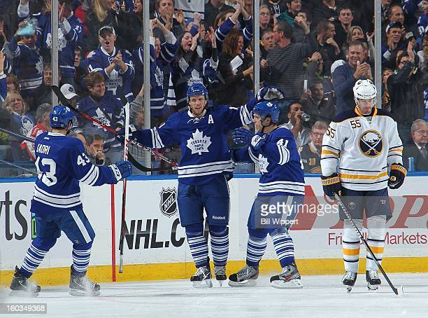 Jay McClement of the Toronto Maple Leafs celebrates his first period goal against the Buffalo Sabres with teammates Nazem Kadri and Nikolai Kulemin...