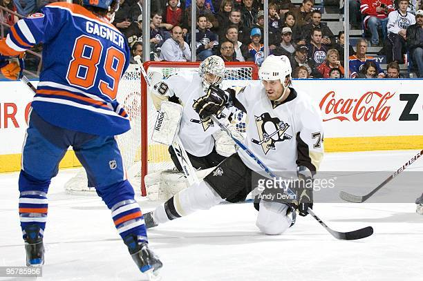 Jay McKee and MarcAndre Fleury of the Pittsburgh Penguins go down to stop a shot from Sam Gagner of the Edmonton Oilers at Rexall Place on January 14...